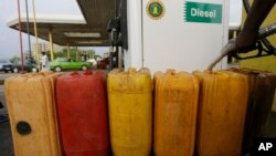 FILE - A man fills containers with diesel at a petrol station in Abuja, Nigeria, May 26, 2015. The new government of President Muhammadu Buhari said it would get country's four refineries back up and running.