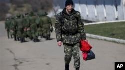 21일 러시아 군 행렬을 지나쳐 홀로 걷고있는 우크라이나 병사.