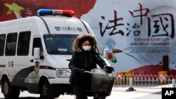 "A woman and a police van pass a Chinese government propaganda billboard that reads ""China Rule By Law"" on a street in Beijing, Dec. 28, 2016. Infuriated by a decision by Beijing prosecutors to drop charges in a high-profile police brutality case, university alumni circles across China mobilized online this week with petition drives, posing to China's government an unusual challenge with its white-collar makeup and swiftly expanding nationwide reach."