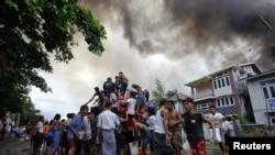 Warga di negara bagian Rakhine mengambil air dari truk pemadam kebakaran untuk memadamkan kebakaran rumahnya dalam bentrokan antara ummat Budha dan muslim Rohingya (10/6).