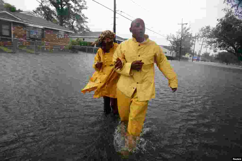 A man and a woman walk through flood waters on St. Roch ave. as Hurricane Isaac makes land fall in New Orleans, Louisiana August 29, 2012.
