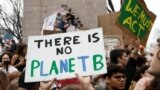 FILE - Students hold placards during a demonstration against climate change at Columbus Circle in New York, March 15, 2019.
