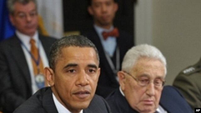 President Barack Obama speaks during a meeting about the new START Treaty in the Roosevelt Room of the White House in Washington as former Secretary of State Henry Kissinger (r) looks on, 18 Nov 2010
