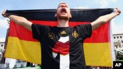 German soccer player Per Mertesacker celebrates on stage at the German team victory ceremony, near the Brandenburg Gate in Berlin, Germany, July 15, 2014.