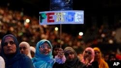 Seorang perempuan memegang plakat bertuliskan 'Perdamaian' dalam sebuah konferensi perdamaian Islamis di Wembley Arena, London. (Foto: Dok)