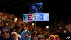 FILE - A placard reading 'Peace' is held by a woman during an Islamic peace conference at Wembley Arena in north-west London, Saturday, Sept. 24, 2011.