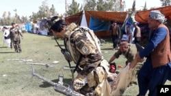 资料照:阿富汗拉什卡尔加地区发生多起爆炸后,人们抬走一名伤员。(2019年3月23日)