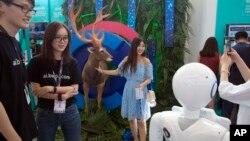 2018年7月4日在北京举行的2018百度AI开发者大会期间,一名女子在鹿的复制品旁边摆拍,尝试机器视觉识别仪器。该活动旨在将开发商,企业和个人同百度的人工智能资源联系起来。