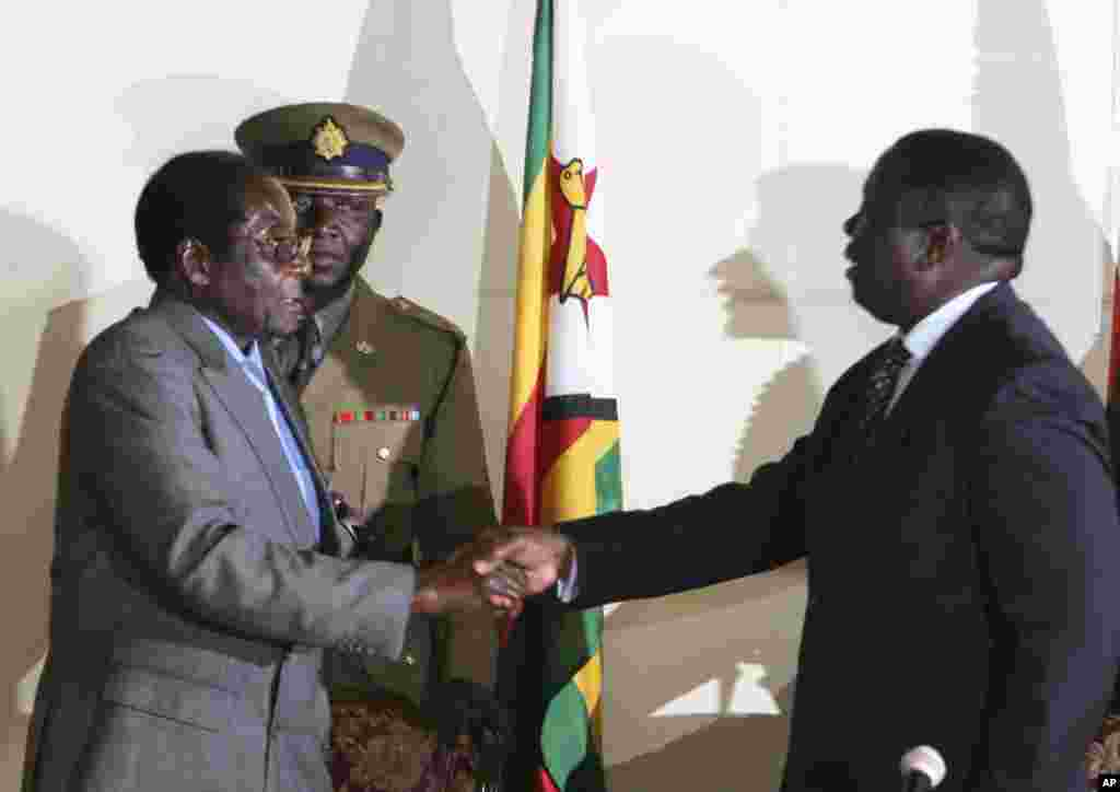 President Robert Mugabe, left, shakes hands with Morgan Tsvangirai, leader of the main opposition in Zimbabwe at the signing of a memorandum of understanding between the two parties.