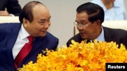 នាយករដ្ឋមន្ត្រីវៀតណាម លោក ង្វៀន សួនហ៊្វុក (Nguyen Xuan Phuc) (ឆ្វេង) និយាយជាមួយនឹងលោកនាយករដ្ឋមន្ត្រី ហ៊ុន សែន នៅក្នុងពិធីចុះហត្ថាលេខាមួយ នៅការិយាល័យនាយករដ្ឋមន្ត្រី ក្នុងរាជធានីភ្នំពេញ កាលពីថ្ងៃអង្គារ ទី២៥ ខែមេសា ឆ្នាំ២០១៧។ ((REUTERS/Samrang Pring)