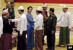 Aung San Suu Kyi, center, shakes hands with Senior General Min Aung Hlaing after the presidential handover ceremony in Naypyitaw, Myanmar, Wednesday, March 30, 2016. (Nyein Chan Naing/Pool Image via AP)