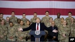 Presiden Donald Trump (tengah) bersama Presiden Afghanistan Ashraf Ghani dan Kepala Staf Gabungan Militer AS Jenderal Mark Milley (di belakangnya, kanan), dalam kunjungan kejutan Hari Thanksgiving di bandara Bagram, Afghanistan, Kamis, 28 November 2019.