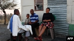 A South African miner and his family sit outside their home in Marikana, September 9, 2012.