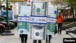 People dressed as blocks of currency notes walk along a street as part of a marketing campaign in Moscow, April 28, 2014.
