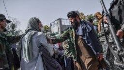 Anggota Taliban menghentikan protes perempuan untuk hak-hak perempuan di Kabul, 21 Oktober 2021. Taliban dengan keras menindak liputan media tentang protes hak-hak perempuan di Kabul pada 21 Oktober pagi, memukuli beberapa wartawan. (BULENT KILIC / AFP)
