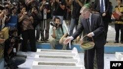 Đại sứ Hà Lan tại Indonesia, ông Tjeerd de Zwaan (phải) rải các cánh hoa lên những ngôi một trong nghĩa trang ở Rawgede, Indonesia trong buổi lễ tưởng niệm