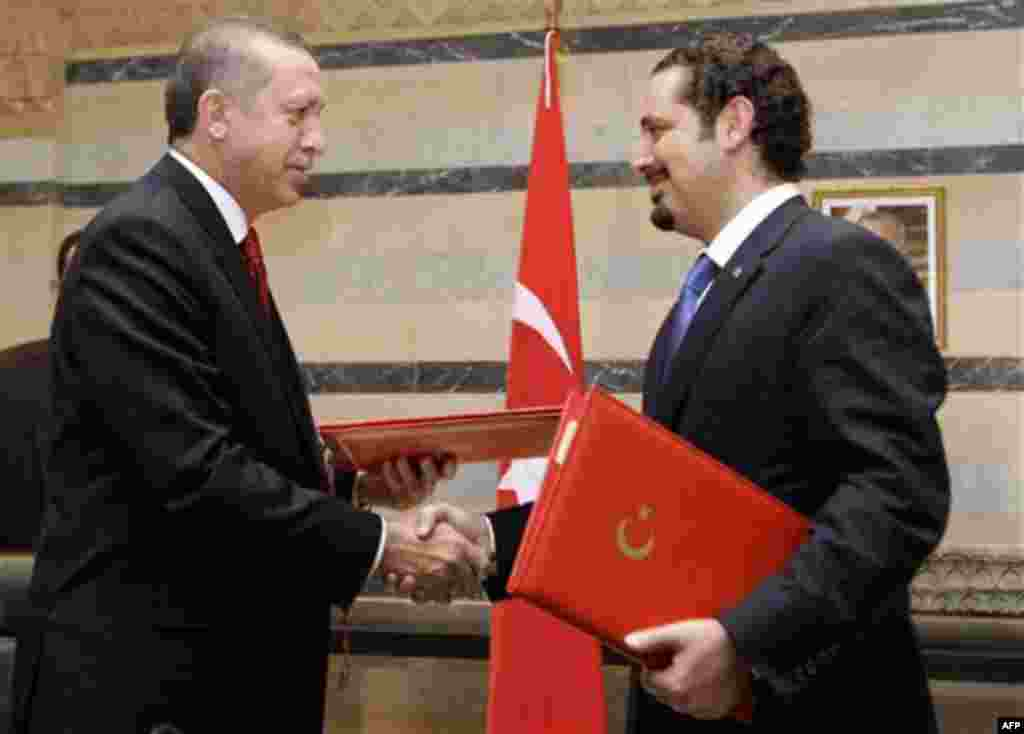 Lebanese Prime Minister Saad Hariri, right, exchanges signed agreements with his Turkish counterpart Recep Tayyip Erdogan, left, at the Government House in Beirut, Lebanon, Wednesday, Nov. 24, 2010. Erdogan arrived in Beirut on Wednesday on a two-day visi