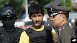 Police officers escort a key suspect in last month's Bangkok bombing, yellow shirt, identified by Thai police as Yusufu Mierili, also as Yusufu Mieraili, traveling on a Chinese passport, but his nationality remains unconfirmed, outside Hua Lamphong railwa