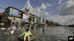 A Thai woman sits on an inflated tire as people leave flooded areas in Bangkok, Thailand, October 26, 2011.