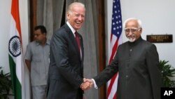 U.S. Vice President Joe Biden (L) shakes hands with Indian Vice President Hamid Ansari as they pose for the media before a meeting in New Delhi, India, July 23, 2013.