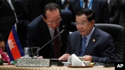Cambodia's Prime Minister Hun Sen, talks to Cambodia's Foreign Minister Hor Namhong before the plenary session meeting for 26th ASEAN Summit in Kuala Lumpur, Malaysia, on Monday, April 27, 2015. (AP Photo/Joshua Paul)
