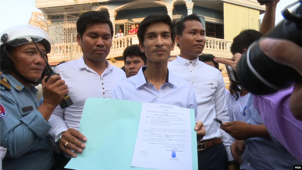 Srey Chamroeun, who led students group dressing in CNRP's uniform, shows his petition to journalists. (Leng Len/VOA Khmer).