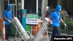 Para petugas mendoron tangki oksigen di RSUP Dr. Sardjito di Yogyakarta, Minggu, 4 Juli 2021. (Foto: Kalandra/AP Photo)