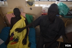 Michael Chieng Bol, right, holds his hand on his brother Simon's stomach, which is in need of further surgery following an operation to remove his appendix, in Juba Teaching Hospital, South Sudan's largest medical facility, May 23, 2016. (J. Patinkin/VOA)