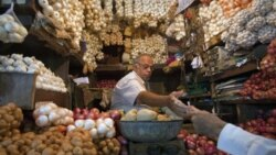 A vendor exchanges money with a customer at a shop selling garlic, onions and potatoes at a wholesale market in Mumbai. India's recent economic rise has expanded its role and deepened its stake in shaping the international system.