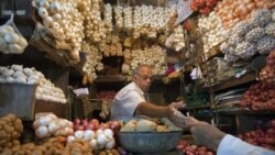 A vendor exchanges money with a customer at a shop selling garlic, onions and potatoes at a wholesale market in Mumbai. India's food price index rose 8.76 percent in the year to April 16, government data showed.