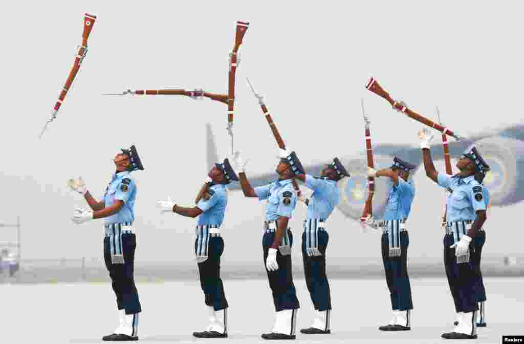 Indian Air Force soldiers throw their rifles during the full-dress rehearsal for Indian Air Force Day at the Hindon air force station on the outskirts of New Delhi.