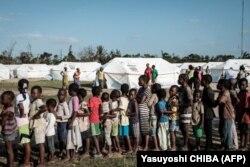 Anak-anak mengantri untuk menerima distribusi makanan dari supermarket lokal di pusat evakuasi di Dondo, sekitar 35 km sebelah utara dari Beira, Mozambik, pada 27 Maret 2019. (Foto: Yasuyoshi CHIBA/AFP)