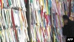 Южнокореец смотрит в сторону Северной Кореи через заграждение из колючей проволоки, на котором вывешены послания, призывающие к объединению страны. Фотография сделана в южнокорейской деревне Панмунчжон, расположенной на демаркационной линии, разделяющей д