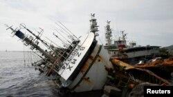 Kapal nelayan yang terbalik akibat Topan Meranti di Kaohsiung, Taiwan (15/9). (Reuters/Tyrone Siu)