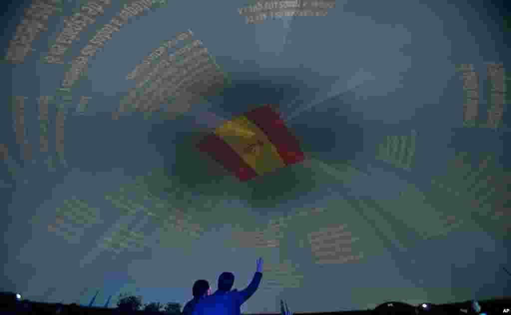 Seorang pria mengangkat tangan di bawah sebuah bendera Spanyol di ibukota Madrid, Warga Spanyol akan merayakan HUT konstitusi Spanyol tanggal 6 Desember.