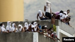 지난 2015년 4월 베네수엘라 카라카스의 교도소에서 폭동이 발행한 가운데 수감자들이 지붕 위로 올라가 있다. (자료사진)