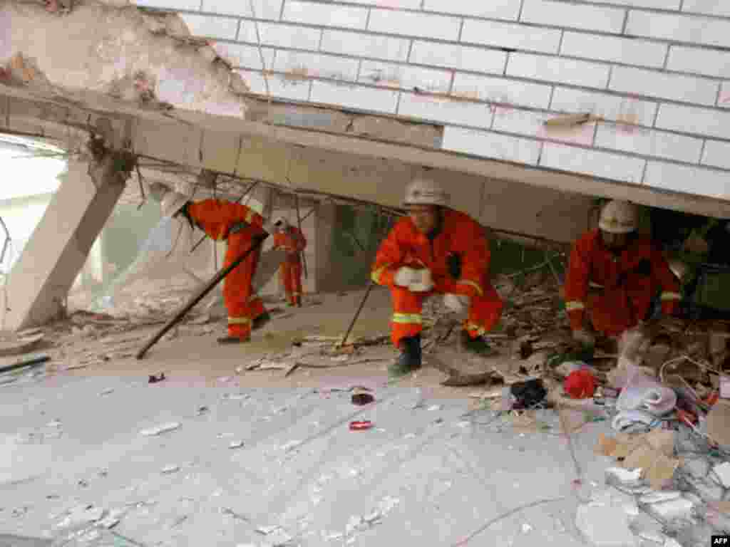 Rescuers search for survivors from the ruins of a damaged building after an earthquake hit Yingjiang county, Yunnan province March 11, 2011. The 5.8-magnitude earthquake has left at least 25 people dead and 250 others injured, Xinhua News Agency reported.