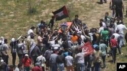 支持巴勒斯坦的抗议者6月5日在叙以边界抬着死于以军射击的人