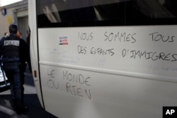 "France Migrants: Police officer walks by a graffiti reading ""We Are All Children of Migrants' Children, The World or Nothing"" after they evacuate migrants camped out in the empty Jean Jaures school in northeast Paris, France, Wednesday, May 4, 2016."