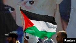 Người Palestine đứng trước 1 tấm áp phích in hình Mohammed Abu Khudair trong tang lễ của em ở Shuafat, 4/7/2014.