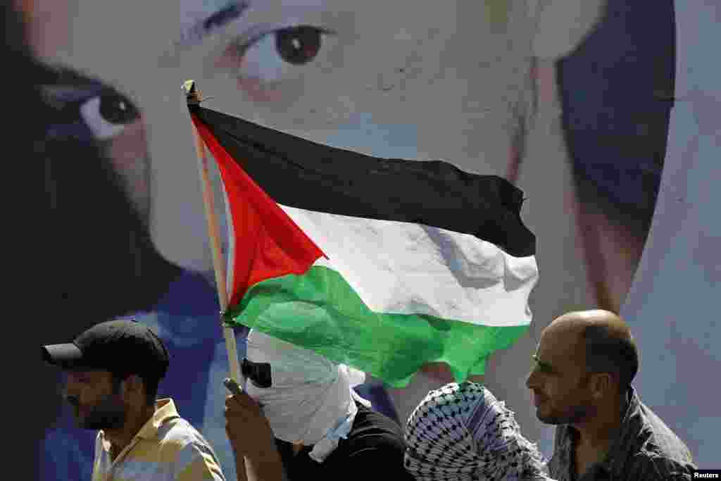 Palestinians look on as they stand in front of a poster depicting 16-year-old Mohammed Abu Khudair during his funeral in Shuafat, an Arab suburb of Jerusalem, July 4, 2014.