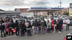 纽约布鲁克林地区加汽油顾客手提油罐步行前来加油站等候开门,汽车在路边排成长队