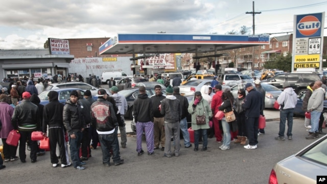 Gas customers on foot with portable containers and lines of vehicles wait for gas pumps to open at a service station, November 3, 2012 in the Brooklyn borough of New York.