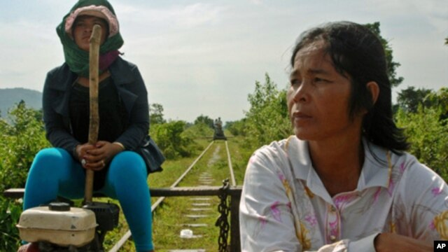 "Riding the rails in western Cambodia: The driver of a ""flying carpet"" and her passenger head west towards the town of Pursat in central Cambodia along the buckled line in late October, closely followed by another flying carpet. This line will be upgraded"