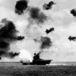Smoke rises from the Yorktown after a Japanese bomber hit the American aircraft carrier in the Battle of Midway in June 1942. Bursts of anti-aircraft fire fill the air.