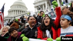 Protesters urge Congress to pass a bill that will allow undocumented immigrants who were brought to America as children to permanently stay in the country, on the Senate steps in Washington, Dec. 6, 2017.