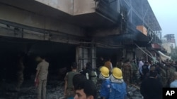 Trabajadores de emergencia buscan apagar el fuego tras la explosión del coche bomba que afectó cerca del consulado estadounidense en Erbil.