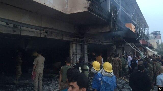 Trabajadores de emergencia buscan apagar el fuego tras la explosi�n del coche bomba que afect� cerca del consulado estadounidense en Erbil.