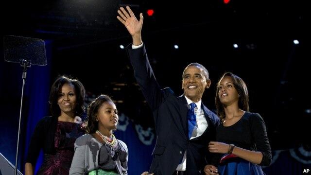 Presiden Barack Obama melambaikan tangan kepada para pendukungnya saat berada di panggung bersama ibu negara, Michelle Obama dan kedua putrinya, Malia dan Sasha untuk memberikan sambutan kemenangan di Chicago, (7/11).