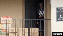 یک عضو خانواده قرنطینه شده در حال برداشتن جعبه های مواد غدایی که صلیب سرخ و بانک غذایی شمال تگزاس آنها را تحویل داده است
